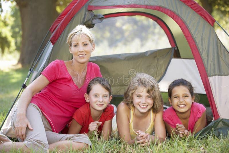 Grupp av flickor med modern som har gyckel i tält i bygd arkivfoton