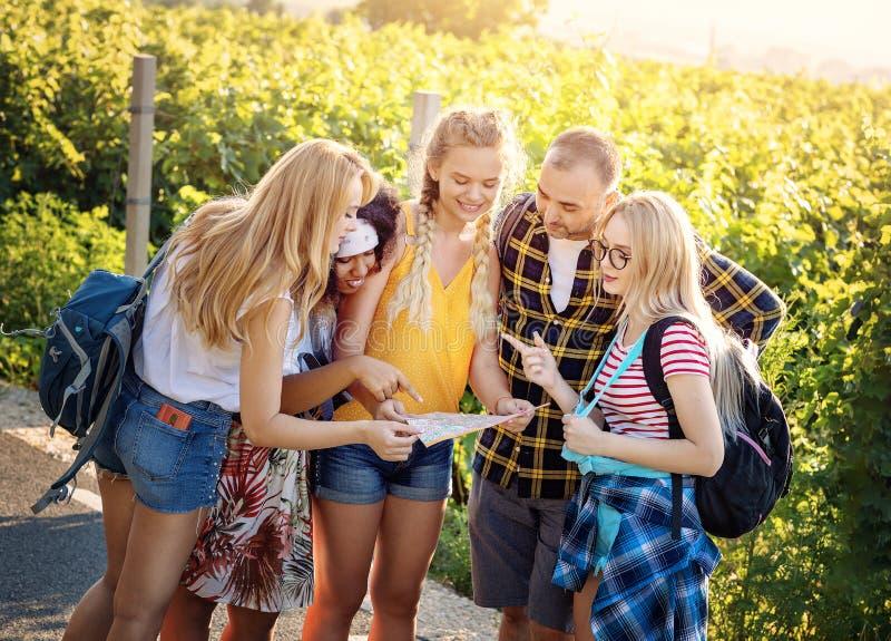 Grupp av flickor som frågar en man vägen, medan rymma en översikt Grupp av tonårs- vänner som utanför tycker om sommardag tillsam royaltyfri bild