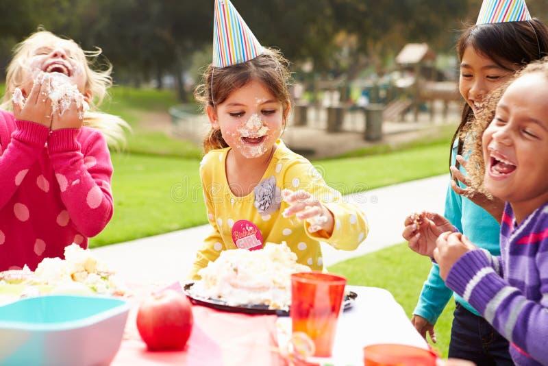 Grupp av flickor som har det utomhus- födelsedagpartiet arkivbild