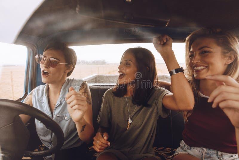 Grupp av flickor som har gyckel i bilen arkivfoto