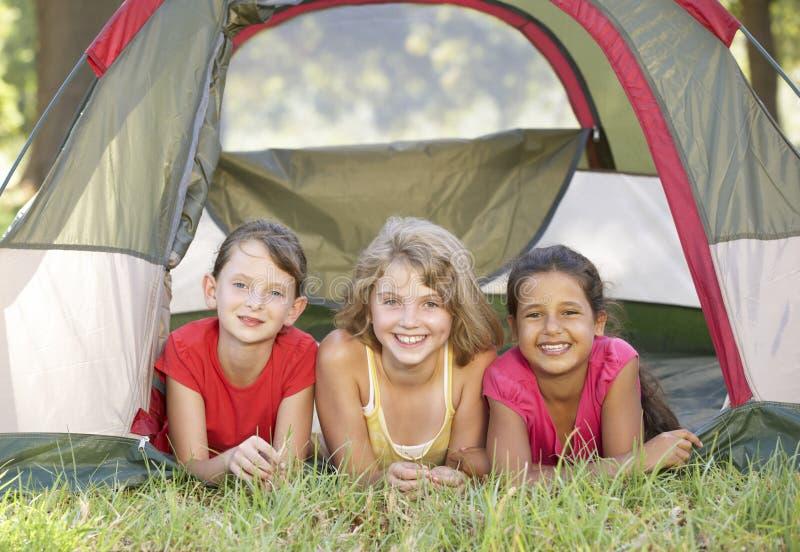 Grupp av flickor som har gyckel i tält i bygd arkivfoton