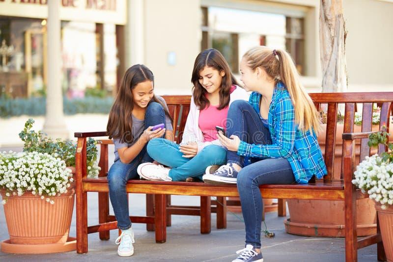 Grupp av flickor som sitter i galleria genom att använda mobiltelefoner royaltyfria bilder