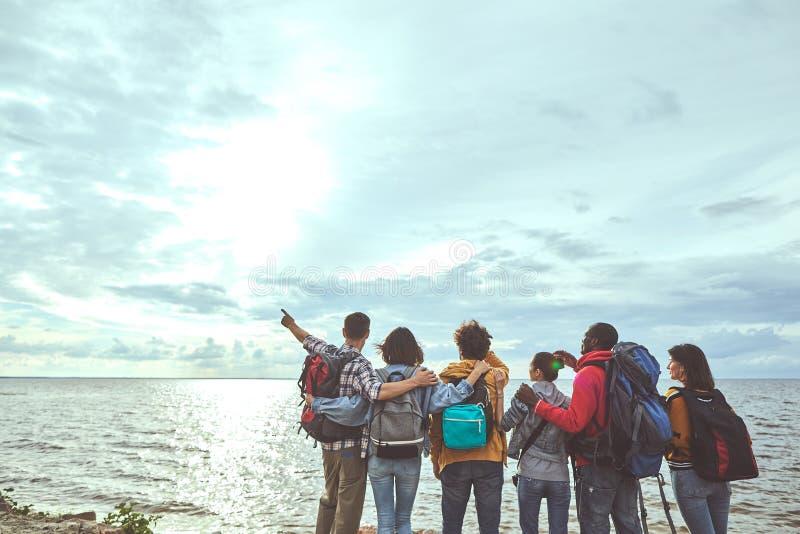 Grupp av folk som ser solen och havet royaltyfria bilder