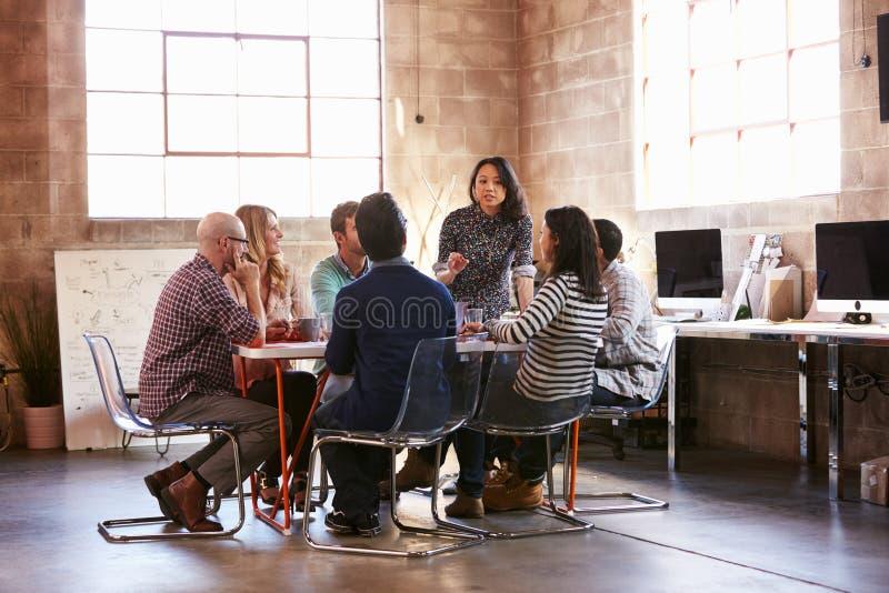 Grupp av formgivare som har möte runt om tabellen i regeringsställning royaltyfri foto