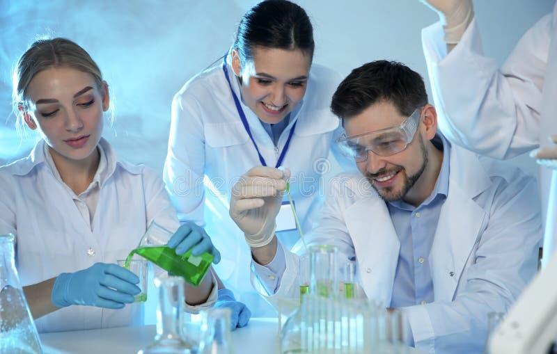 Grupp av forskare som arbetar i kemilaboratorium royaltyfri foto