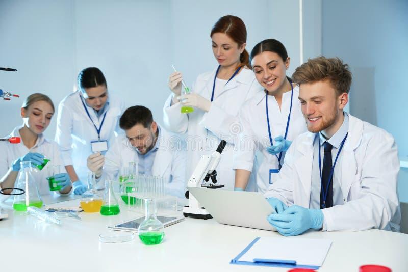 Grupp av forskare som arbetar i modernt laboratorium royaltyfri bild