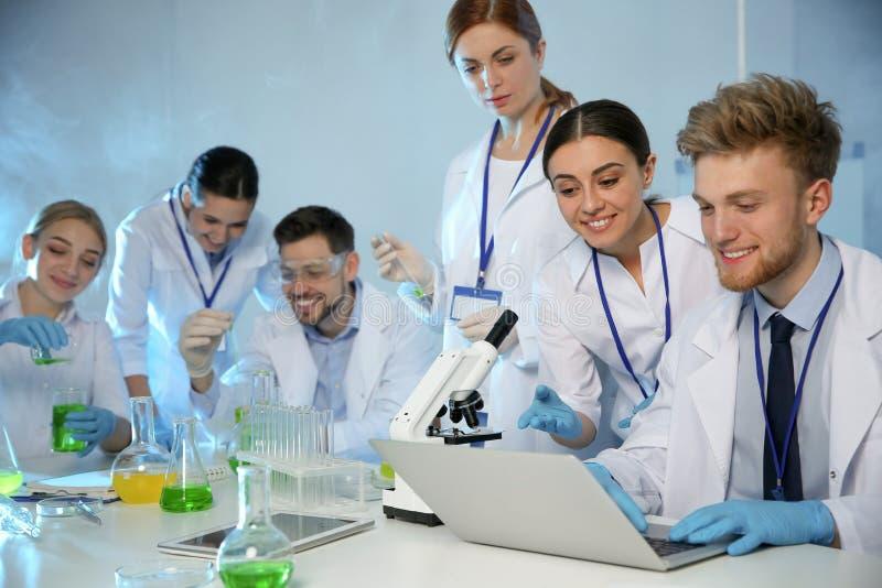 Grupp av forskare som arbetar i modernt laboratorium royaltyfri foto