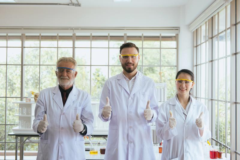 Grupp av forskarefolk som står upp och visar tummen tillsammans, i laboratorium, lyckad teamwork och att arbeta för forskning royaltyfri fotografi