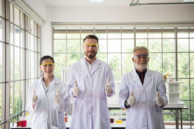 Grupp av forskarefolk som står upp och visar tummen tillsammans i laboratorium, lyckad teamwork och resercharbete royaltyfri bild