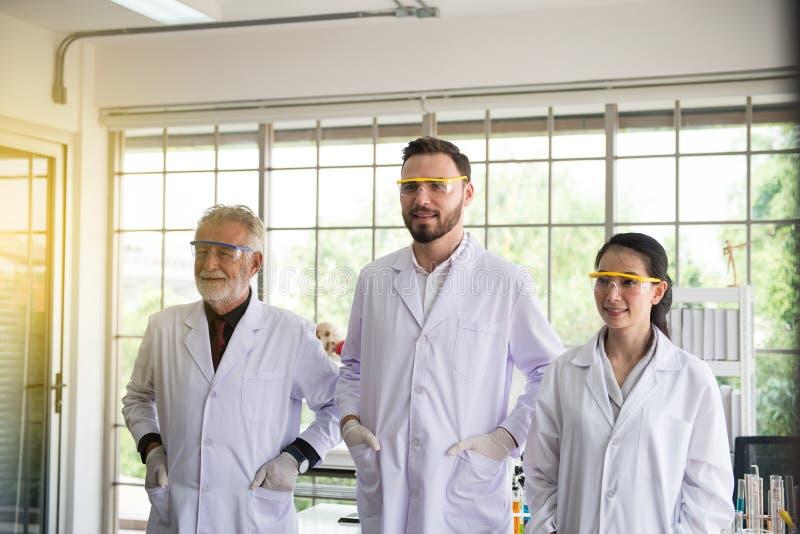 Grupp av forskarefolk som tillsammans står i laboratorium, lyckad teamwork och resercharbete royaltyfri bild