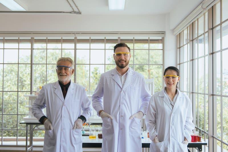 Grupp av forskarefolk som tillsammans står i laboratorium, lyckad teamwork och resercharbete royaltyfri fotografi