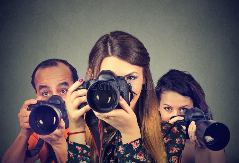 Grupp av fotografer med yrkesmässiga kameror royaltyfri fotografi