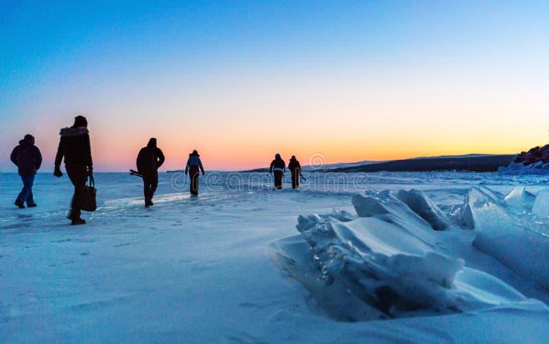 Grupp av fotografhandelsresande som går på djupfrysta Lake Baikal, Ryssland Jaktsoluppgång i vinter arkivbilder
