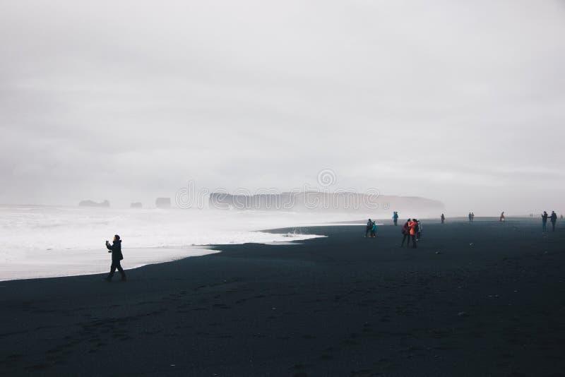 Grupp av fotvandrare som omkring strosar och tar bilder på kusten av det härliga havet royaltyfri foto