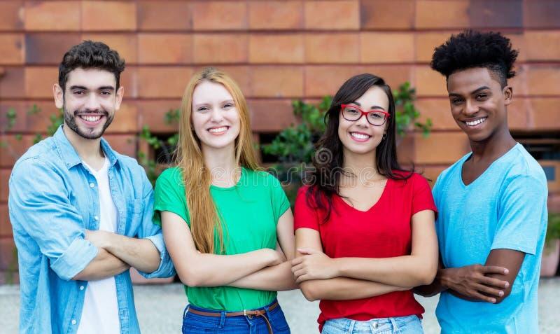 Grupp av fyra afrikan och latin - amerikan och caucasian unga vuxna m?nniskor royaltyfri fotografi