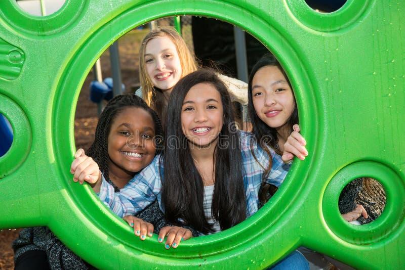 Grupp av fyra barn med kulturell mångfald som tillsammans spelar royaltyfri foto