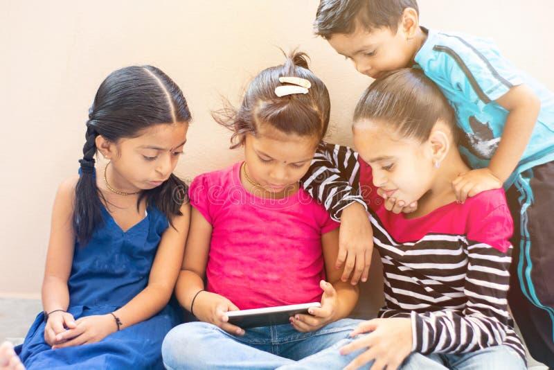 Grupp av fyra gulliga lilla indiska ungar som håller ögonen på den enkla mobila enheten arkivfoto