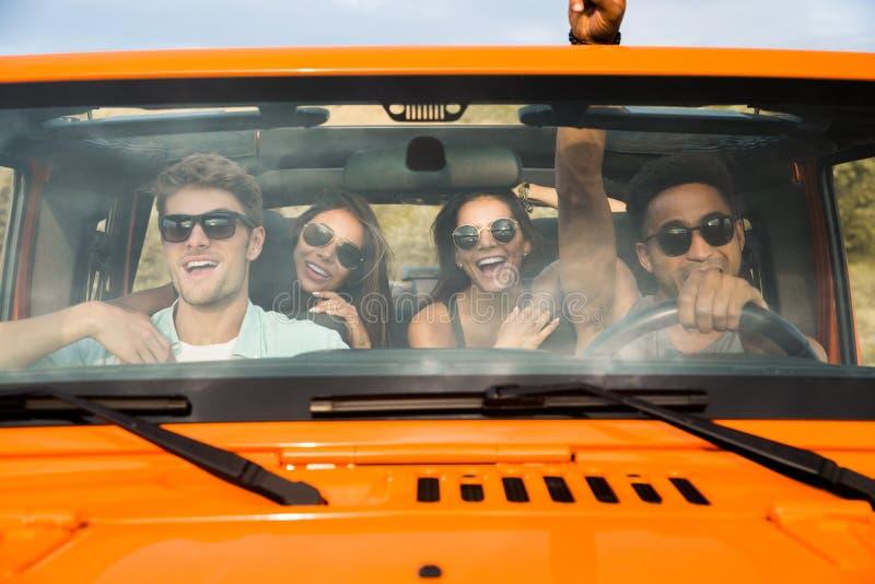 Grupp av fyra lyckliga unga vänner som sitter i en bil royaltyfria bilder