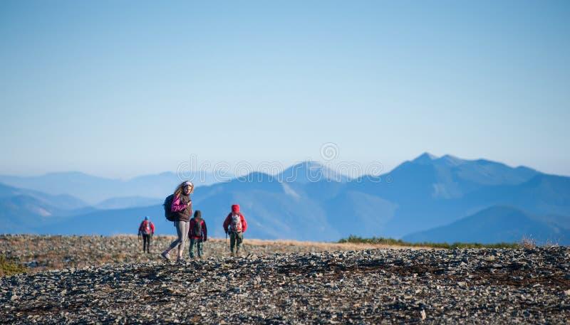 Grupp av fyra personer som går på det steniga berget plato fotografering för bildbyråer