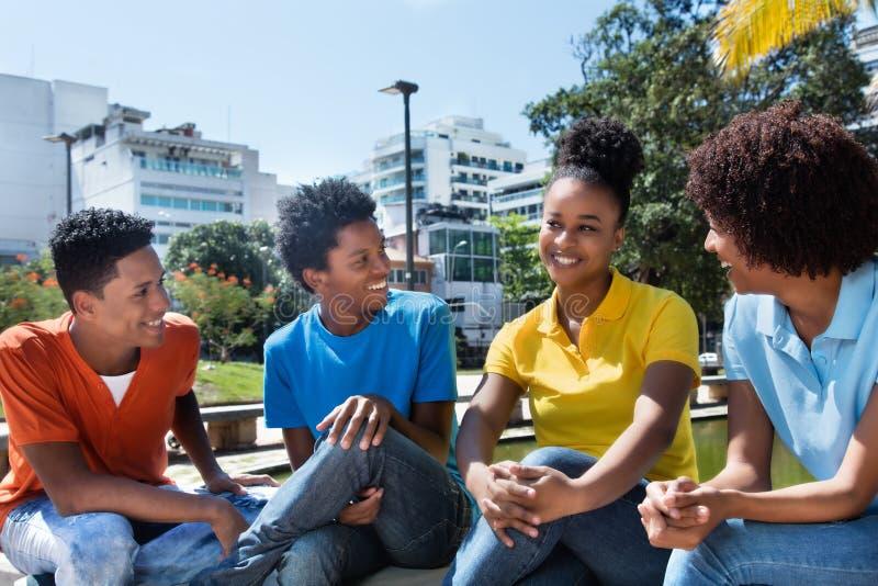 Grupp av fyra talande latin - amerikanskt ungt vuxet utomhus- royaltyfri foto