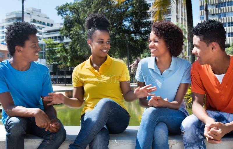 Grupp av fyra talande latin - amerikanskt ungt vuxet utomhus- royaltyfri fotografi
