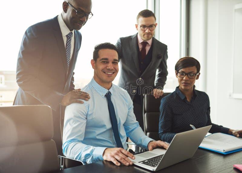 Grupp av fyra unga affärspersoner i regeringsställning arkivfoton