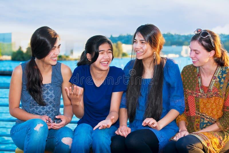Grupp av fyra unga kvinnor som tillsammans talar vid sjön royaltyfri bild