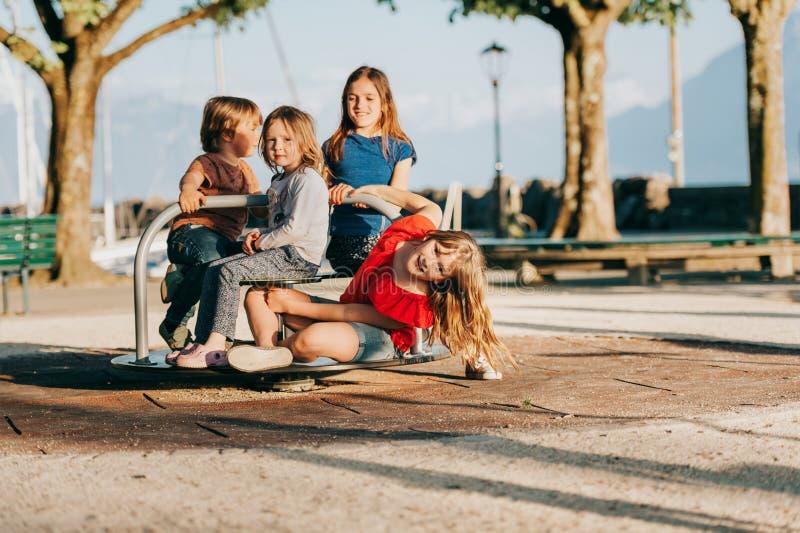 Grupp av fyra ungar som har gyckel på lekplats arkivbild