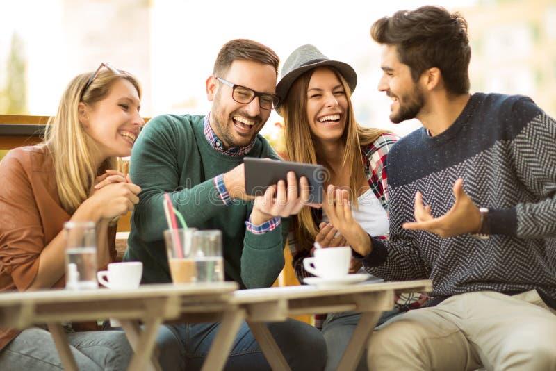 Grupp av fyra vänner som har ett kaffe tillsammans royaltyfri foto