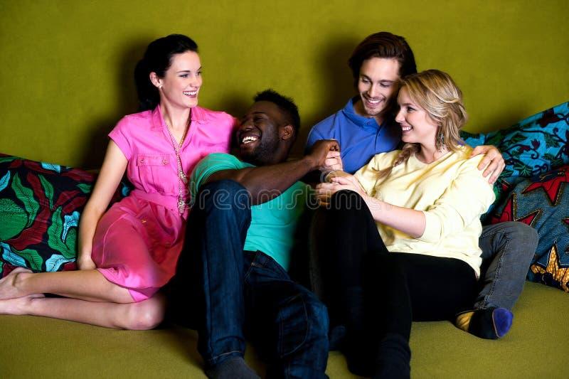 Grupp av fyra vänner som har gyckel royaltyfria bilder