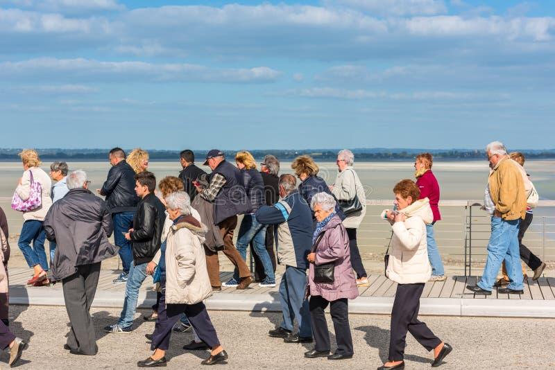 Grupp av gamla människor som besöker den Mont Saint Michel kloster royaltyfria foton