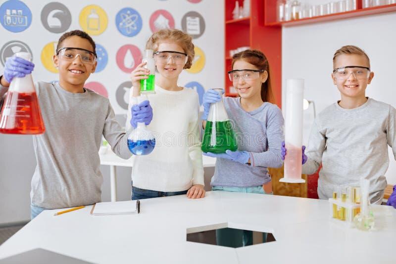 Grupp av glade studenter som poserar med kemiska flaskor i labb royaltyfri fotografi