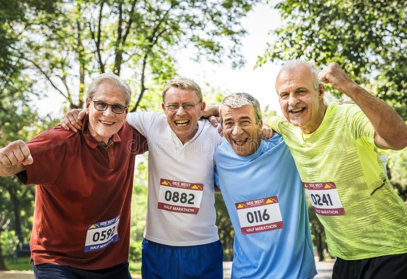 Grupp av gladlynta höga löpare på parkera arkivfoto