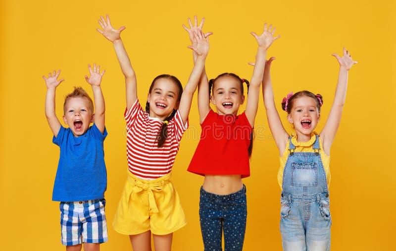 Grupp av gladlynta lyckliga barn p? kul?r gul bakgrund arkivbilder