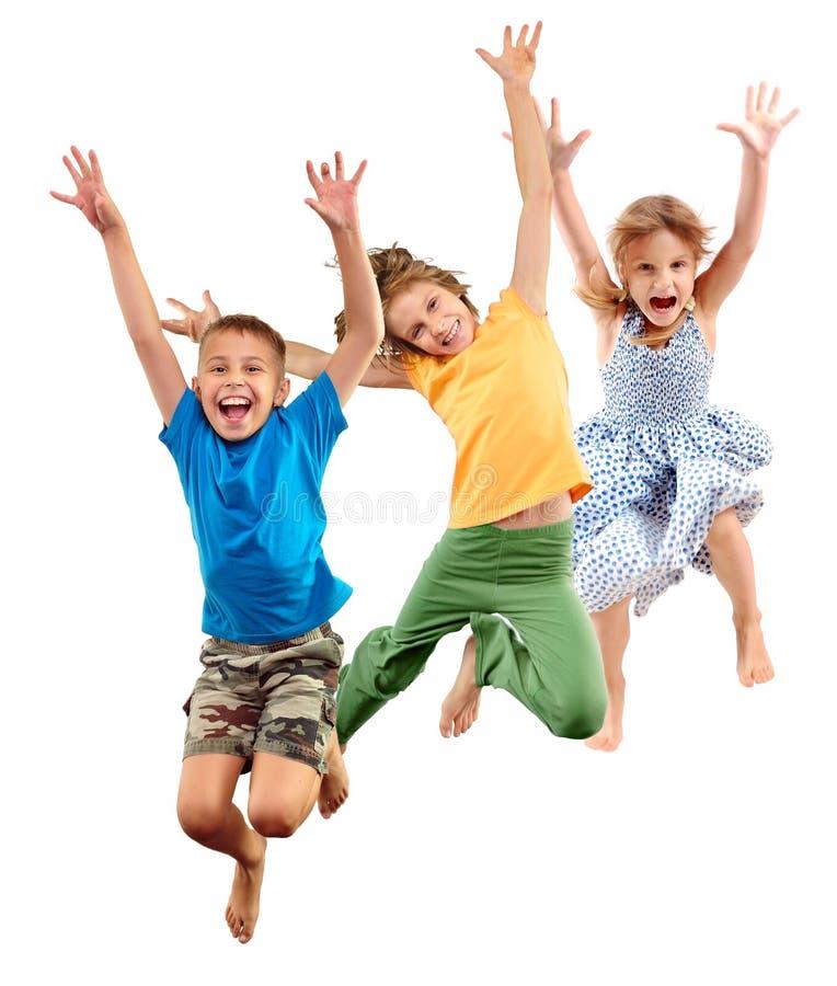 Grupp av gladlynta sportive barn för lycklig barefeet som hoppar och dansar arkivbilder