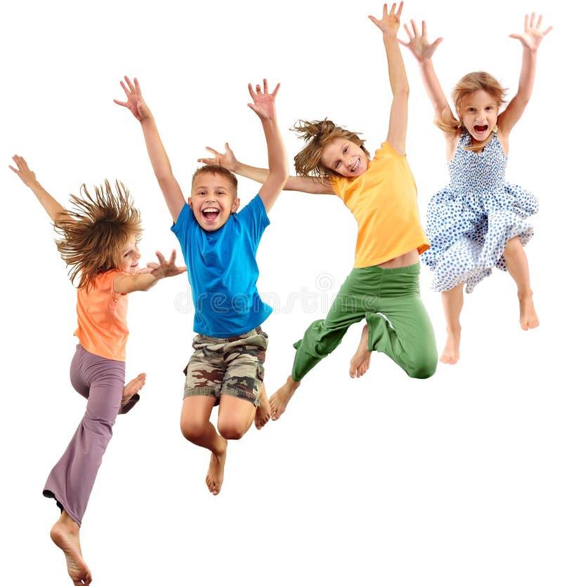 Grupp av gladlynta sportive barn för lycklig barefeet som hoppar och dansar arkivfoto
