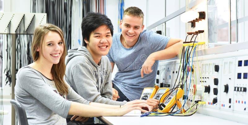Grupp av gladlynta unga studenter i yrkesutbildning och tra arkivfoton
