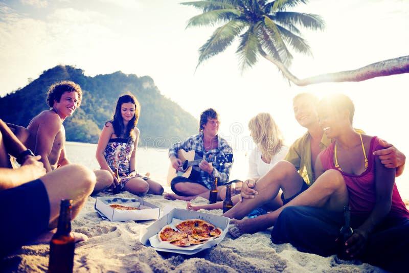 Grupp av gladlynta ungdomarsom kopplar av på en strand arkivfoto