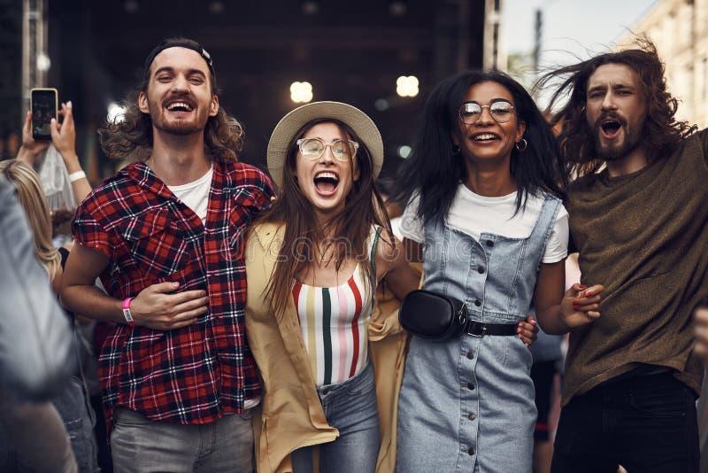Grupp av gladlynta vänner som har gyckel på den utomhus- konserten royaltyfria foton