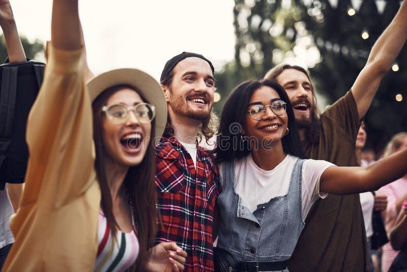 Grupp av gladlynta vänner som utomhus spenderar tid royaltyfri bild