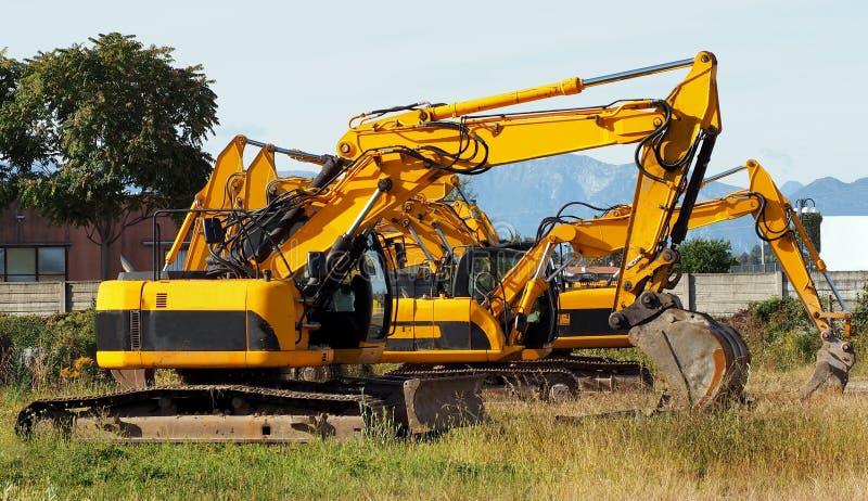 Grupp av grävskopor på ett fält i en nybyggnadplats arkivfoto