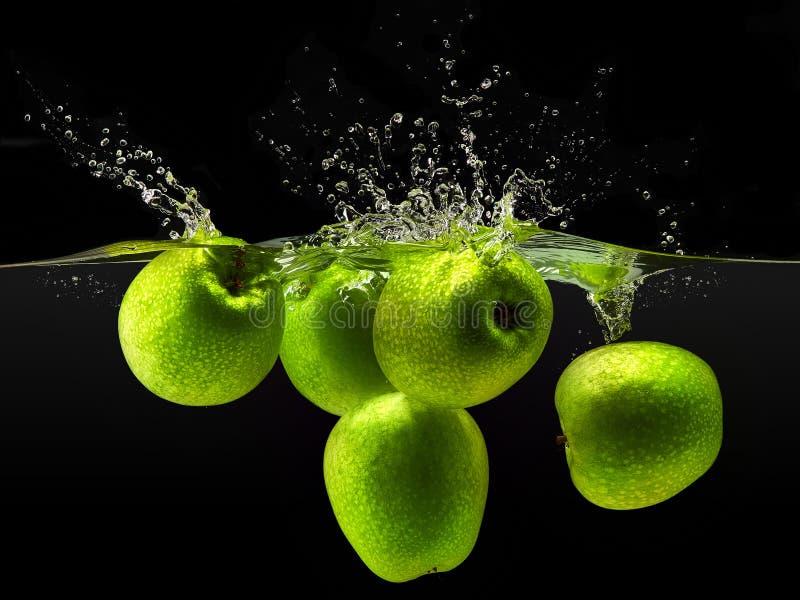Grupp av gröna äpplen som faller i vatten på svart royaltyfria bilder