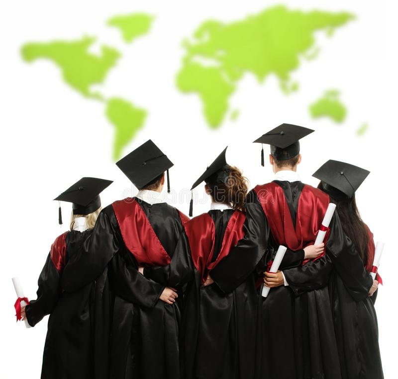 Grupp av graderade studenter mot världskarta arkivbild