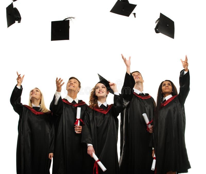 Grupp av graderade studenter som kastar hattar royaltyfri fotografi
