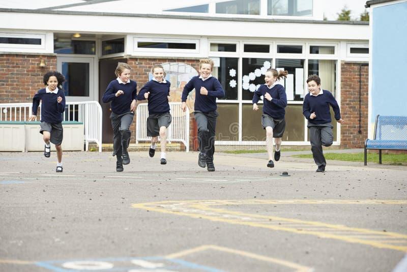 Grupp av grundskolaelever som kör i lekplats arkivfoton