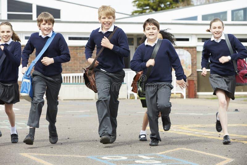 Grupp av grundskolaelever som kör i lekplats royaltyfria foton