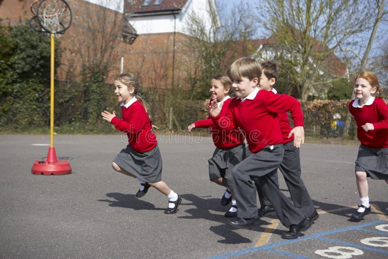 Grupp av grundskolaelever som kör i lekplats royaltyfria bilder