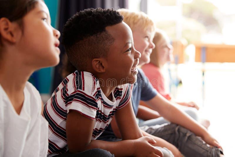 Grupp av grundskolaelever som sitter på golv som lyssnar till läraren royaltyfria bilder