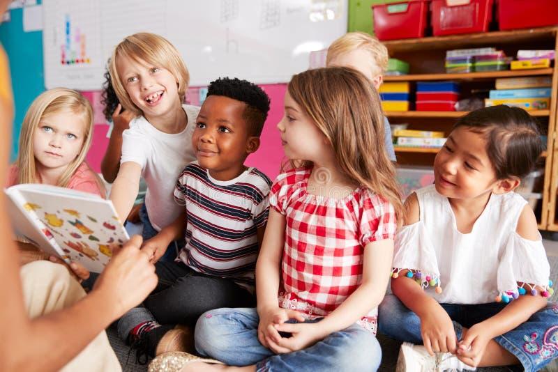 Grupp av grundskolaelever som sitter på golv som lyssnar till lärarinnan Read Story arkivbilder