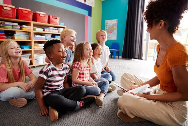 Grupp av grundskolaelever som sitter på golv som lyssnar till lärarinnan Read Story fotografering för bildbyråer